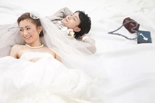 寝転ぶ新郎新婦の写真素材 [FYI02409424]