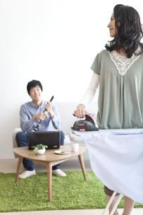 アイロン掛けをする女性とクラリネットを組み立てる男性の写真素材 [FYI02410021]