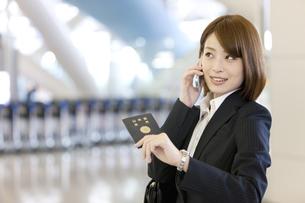 スマートフォンで電話しているビジネスウーマンの写真素材 [FYI02410200]