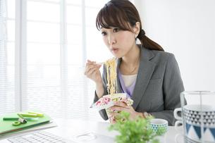 カップラーメンを食べるビジネスウーマンの写真素材 [FYI02411177]