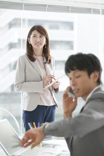 電話をするビジネスマンとタブレットPCを持つ女性の写真素材 [FYI02411394]