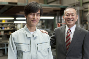 肩に手を置くビジネスマンと作業者の写真素材 [FYI02411633]