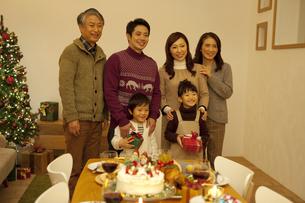 クリスマスプレゼントを持つ3世代家族の写真素材 [FYI02411734]
