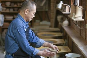 陶芸をするシニア男性の横顔の写真素材 [FYI02411832]