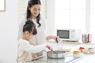 料理をする女の子と母親の写真素材 [FYI02411937]