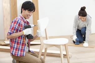 椅子を組み立てる夫婦の写真素材 [FYI02412144]