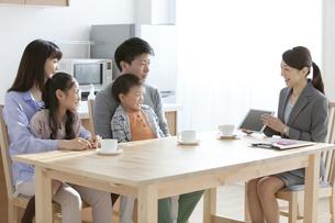 ビジネスウーマンの説明を聞く家族4人の写真素材 [FYI02412211]