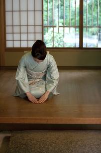 玄関で挨拶する着物姿の女性の写真素材 [FYI02412496]