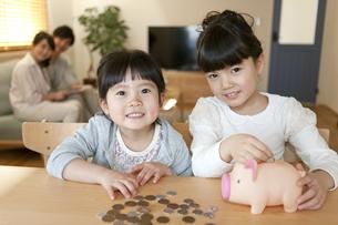 貯金箱にお金を入れる姉妹の写真素材 [FYI02413262]