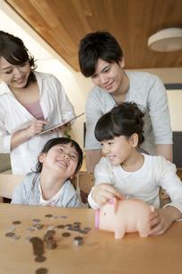 貯金箱と家族の写真素材 [FYI02413377]