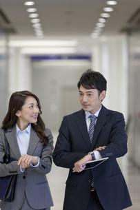 時間を気にするビジネスマンとビジネスウーマンの写真素材 [FYI02414007]