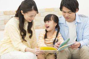 絵本を読む家族の写真素材 [FYI02414258]