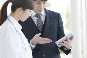 打ち合わせをするビジネスマンと女医の写真素材 [FYI02414464]