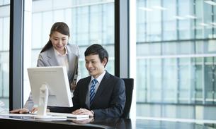 パソコンを見るビジネスマンとビジネスウーマンの写真素材 [FYI02415022]