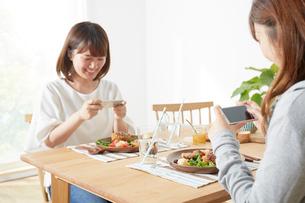 ダイニングテーブル上のコロッケをスマホで撮影する女性たちの写真素材 [FYI02420925]