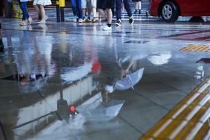 雨で駅の歩道に写りこむ人の流れの写真素材 [FYI02420937]