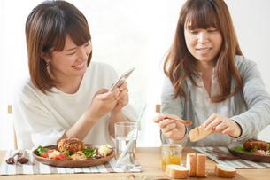 ダイニングテーブル上のパンをスマホで撮影する女性たちの写真素材 [FYI02420949]