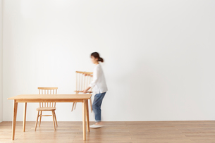 ダイニングテーブルとダイニングチェアを運ぶ女性の写真素材 [FYI02420956]