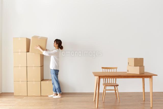 積まれたダンボール箱とテーブルと、箱を運ぶ女性の写真素材 [FYI02420999]