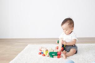 白ラグの上で遊ぶ赤ちゃんの写真素材 [FYI02421024]