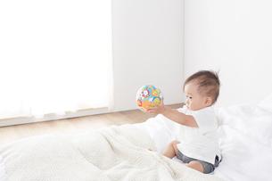 ベッドの上で遊ぶ赤ちゃんの写真素材 [FYI02421025]