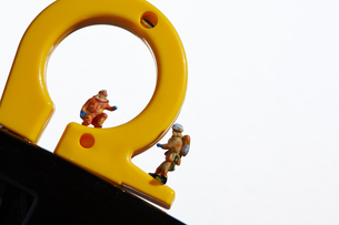 消化器の上で働くミニチュア消防士の写真素材 [FYI02421047]