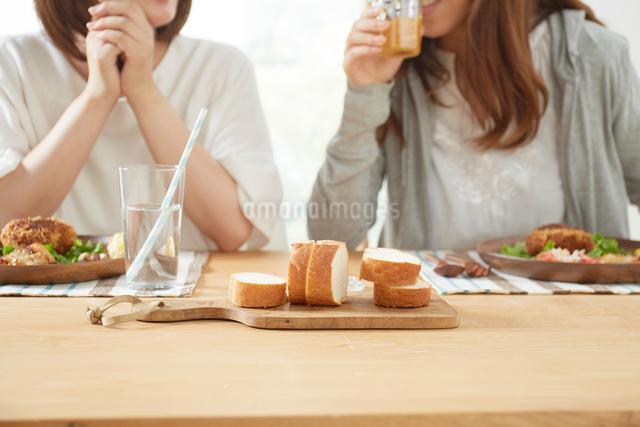 ダイニングテーブル上のパンと女性たちの写真素材 [FYI02421079]