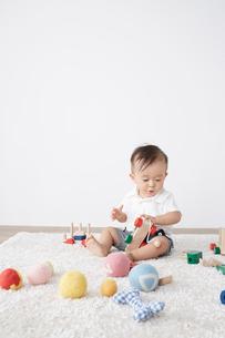 白ラグの上で遊ぶ赤ちゃんの写真素材 [FYI02421080]