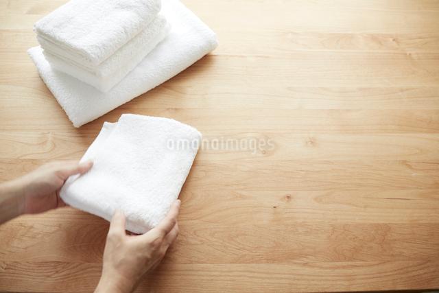 テーブルの上でタオルをたたむ女性の写真素材 [FYI02421107]