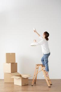 積まれたダンボールと、ペンダントライトを付ける女性の写真素材 [FYI02422218]