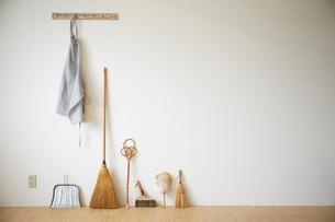 壁にかかったエプロンと掃除道具の写真素材 [FYI02422400]