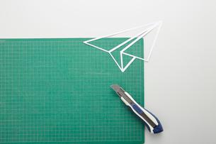 カッティングマットの上の紙ひこうきとカッターのイラスト素材 [FYI02422435]