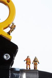 消化器の上で働くミニチュア消防士の写真素材 [FYI02422567]