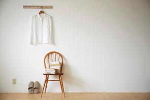 白シャツと椅子に積んだ本にスリッパの写真素材 [FYI02422577]