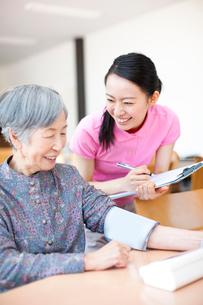 血圧を測るおばあちゃんと介護士の写真素材 [FYI02423263]