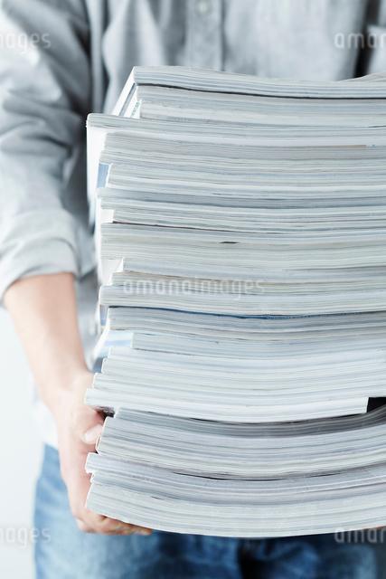 積み重なった雑誌を持つ人の写真素材 [FYI02425746]