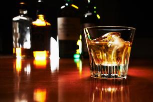 カウンターの上の琥珀色に輝くグラスに入ったロックのウィスキーの写真素材 [FYI02426079]