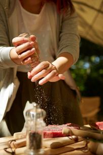 生肉に塩をふる女性の写真素材 [FYI02427389]