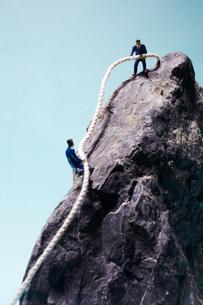 ロープを使って岩を登る2人の男性の写真素材 [FYI02427650]