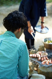 キャンプ場で食材を調理する女性とそれを見守る男性の写真素材 [FYI02427828]