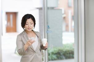 携帯電話を見て出勤するビジネスウーマンの写真素材 [FYI02427963]