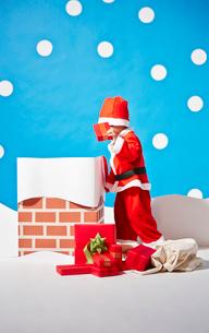 煙突にプレゼントを入れるサンタクロースの格好をする男の子の写真素材 [FYI02428273]