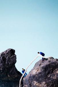 ロープを使って岩を登る2人の男性の写真素材 [FYI02428969]