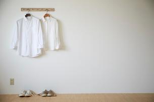 壁にかかった二つのシャツと二つのスニーカーの写真素材 [FYI02428980]