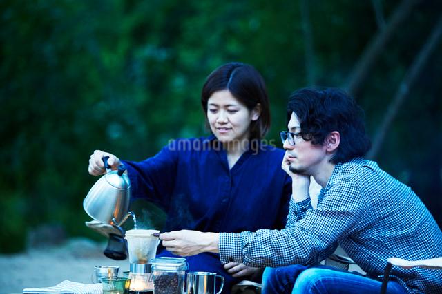 キャンプ場でコーヒーをドリップする男女の写真素材 [FYI02429004]