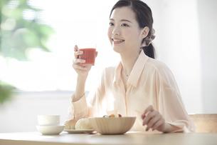 朝食のトマトジュースを持つ若い女性の写真素材 [FYI02430646]