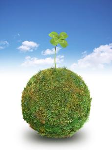 青空背景に草の球体の上にクローバーの葉のイラスト素材 [FYI02431596]
