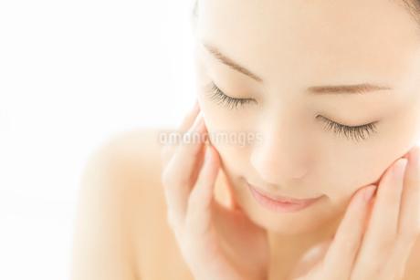 目を閉じ頬に両手を寄せる女性の写真素材 [FYI02433122]