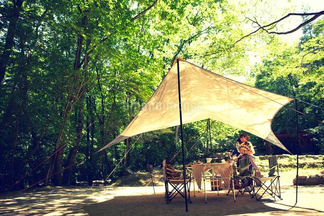 森に貼られたタープと女性の写真素材 [FYI02433359]