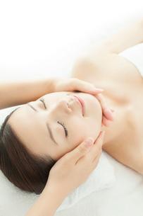 ベッドに仰向けで顔にマッサージを受ける女性の写真素材 [FYI02433626]